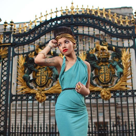 Female model in green dress in front of Buckingham Palace London.