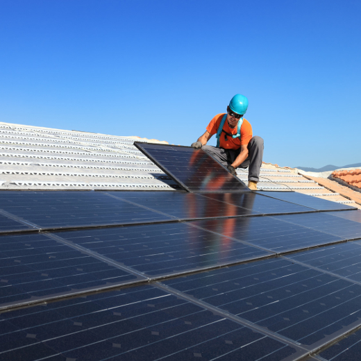 Electrician on rooftop installing solar panels with clear blue sky in background.