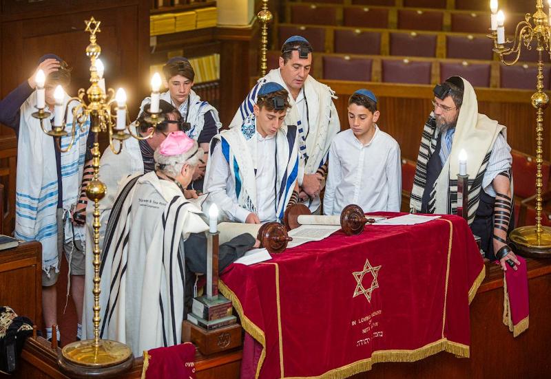 Jewish males surrounding table atBar Mitzvah